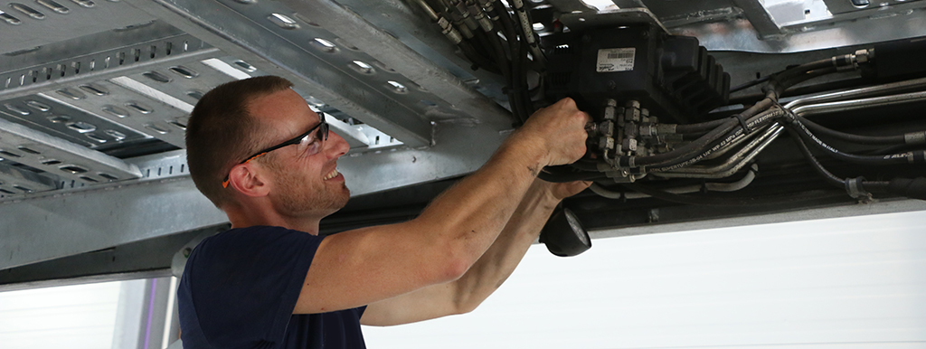 Mechanic performing some maintenance on a LOHR car carrier.